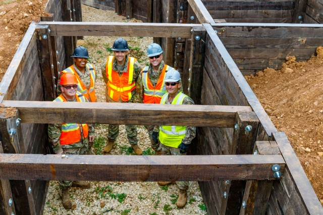 Members of the Joint Multinational Readiness Center's Troop Construction Program stand inside a 100-meter trench they both designed and supervised the construction for on Hohenfels Training Area, Germany, June 4, 2021. The members of the team are (from left): Sgt. 1st Class Chad Spencer, construction management section NCOIC, Sgt. 1st Class Aamira Bryant, the TCP NCOIC/Logistics Planner officer, Maj. Francisco Arocho, TCP officer in charge, Capt. Amauri Padilla, the team's operation officer, and Chief Warrant Officer 2 Raymond Cowden, the team's construction engineering technician. The five-person TCP team, consisting of subject matter experts in the engineering field tasked with maintaining and improving the HTA, teamed up with the 2d Cavalry Regiment's Regimental Engineer Squadron to build the trench, which will be utilized for a number of training events throughout the year, beginning with the European Best Sniper Competition Aug. 5-14 on HTA. The TCP team consists of Army Reserve Soldiers selected based upon their expertise in the construction field serving on Active Duty Operational Support tours to support the 7th Army Training Command mission. (U.S. Army photo by Master Sgt. Ryan C. Matson)