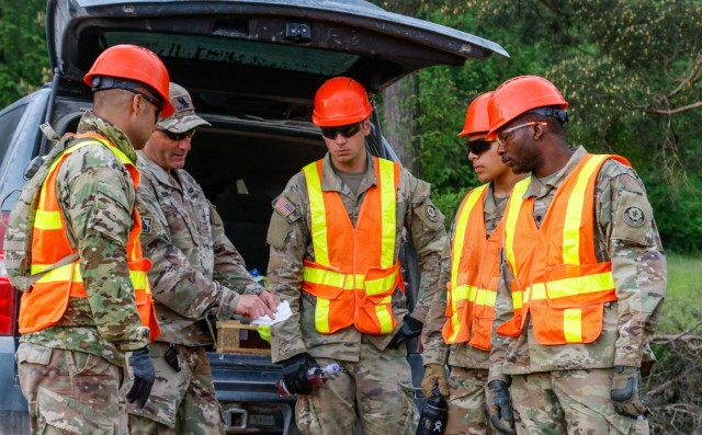 Chief Warrant Officer 2 Raymond Cowden, a construction engineering technician with the Joint Multinational Readiness Center's Troop Construction Program, talks with engineer Soldiers from third platoon, Argonaut Company, Regimental Engineer Squadron, 2nd Cavalry Regiment, during construction of a 100-meter trench at the Hohenfels Training Area, Hohenfels, Germany. The five-person TCP team, consisting of subject matter experts in the engineering field tasked with maintaining and improving the HTA, teamed up with the 2CR RES to build the trench, which will be utilized for a number of training events throughout the year, beginning with the European Best Sniper Competition Aug. 5-14 on HTA. (U.S. Army photo by Master Sgt. Ryan C. Matson)