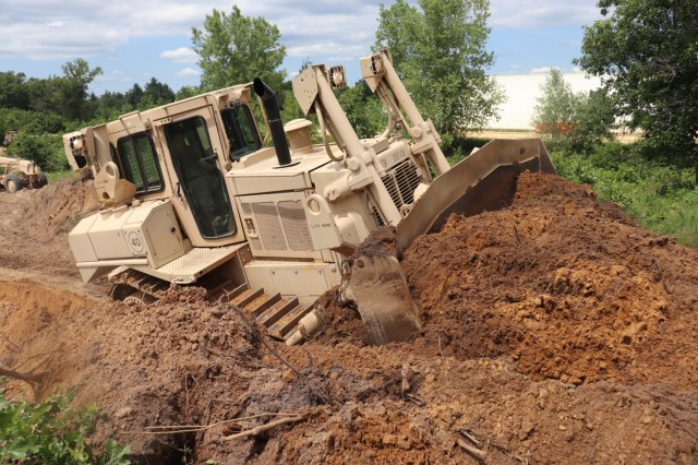 Spc. Seth Abbot with the Wisconsin National Guard's 950th Engineering Company (Route Clearance) operates a bulldozer at a training area July 12, 2021, at Fort McCoy, Wis. The work is part of a troop project coordinated by the Fort McCoy Directorate of Public Works to repurpose and rebuild a training area. The company, which is based in Superior, Wis., is completing the work as part of their annual training. The unit's Soldiers regularly train at Fort McCoy. (U.S. Army Photo by Scott T. Sturkol, Fort McCoy Public Affairs Office)