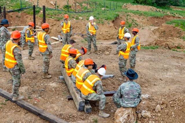 Engineers with the 2nd Cavalry Regiment's Regimental Engineer Squadron and the Joint Multinational Readiness Center's Troop Construction Program conduct a morning meeting before beginning work on a 100-meter trench on Hohenfels Training Area, Hohenfels, Germany, June 4, 2021. The trench will be utilized for a number of training events throughout the year, beginning with the European Best Sniper Competition Aug. 5-14 on HTA. (U.S. Army photo by Master Sgt. Ryan C. Matson)
