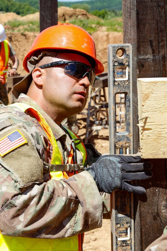 Sgt. Edgar Ortiz, left, a horizontal engineer with third platoon, Argonaut Troop, Regimental Engineering Squadron, 2d Cavalry Regiment, checks the level on the wooden frame of a 100-meter trench on Hohenfels Training Area, Hohenfels, Germany, June 3, 2021. The trench will be utilized for a number of training events throughout the year, beginning with the Fifth Annual European Best Sniper Competition Aug. 5-14 on HTA. (U.S. Army photo by Master Sgt. Ryan C. Matson)