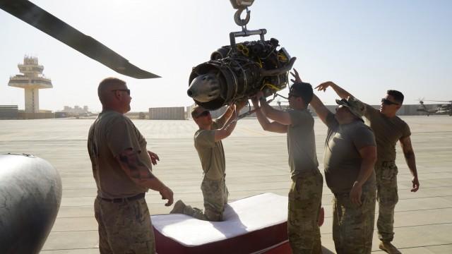 Aircraft mechanics take apart an old UH-60 Black Hawk helicopter engine at Al Asad Air Base, Iraq.