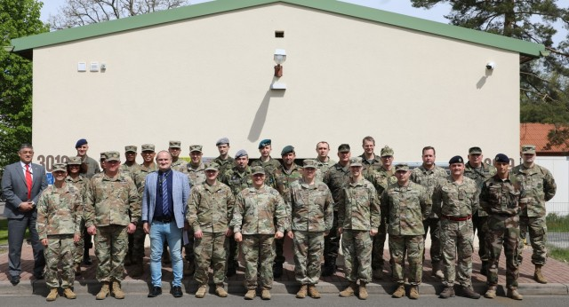 Personnel from the United Kingdom, Germany, France, the Netherlands, Hungary, Poland, Austria, Czech Republic, and Ukraine stand with their U.S. Army Allies in front of the Readiness and Movement Coordination Center, Panzer Kaserne, Germany, during DEFENDER-Europe 21.