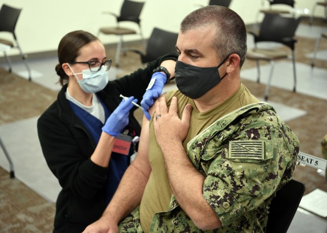 """JOINT BASE SAN ANTONIO-LACKLAND AFB – (Feb. 1, 2021) Chief Quartermaster Harry Warner, of Alvin, Texas, an enlisted classifier/shipping clerk assigned to Navy Talent Acquisition Group (NTAG) San Antonio, receives the initial dose of the COVID-19 vaccine from Air Force 1st Lt. Sarah Caouette, a registered nurse, assigned to the Post Anesthesia Care Unit at Wilford Hall Ambulatory Surgical Center. """"Our command handles applicants and future Sailors from all over the state of Texas,"""" said Warner.  """"It only made sense to get the vaccine and lower my risk of catching it.  My team will be able to continue the mission of placing highly motivated Sailors into the Navy."""" The Defense Department COVID-19 vaccine plan implements a standardized and coordinated strategy for prioritizing, distributing and administering any COVID-19 vaccine through a phased approach to vaccinate active component, reserve component, TRICARE Prime and TRICARE Select beneficiaries, and select DOD civilians and contract personnel authorized to receive immunizations from DOD. NTAG San Antonio's area of responsibility includes two TAOCs which manage more than 34 Navy Recruiting Stations and Navy Officer Recruiting Stations spread throughout 144,000 square miles of Central and South Texas territory. (U.S. Navy photo by Burrell Parmer, NTAG San Antonio Public Affairs/Released)"""