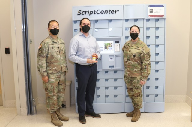 (From left to right) Maj. Lucas Poon, the chief of pharmacy for Weed Army Community Hospital, Ryan Lebowitz, a senior implementation specialist with Asteres, the company that creates ScriptCenter kiosks, and Col. Nancy Parson, the commander of Weed ACH, pose for a photograph with the hospital's new ScriptCenter kiosk July 20 on Fort Irwin. (U.S. Army photo by Kimberly Hackbarth/ Weed ACH Public Affairs)
