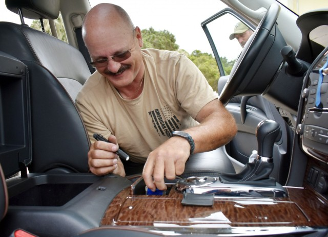 Officer Michael Mancini, a police officer with the Presidio of Monterey Police Department, smiles as he finds hidden contraband during vehicle interdiction training at the Stilwell Community Center, Ord Military Community, July 13.