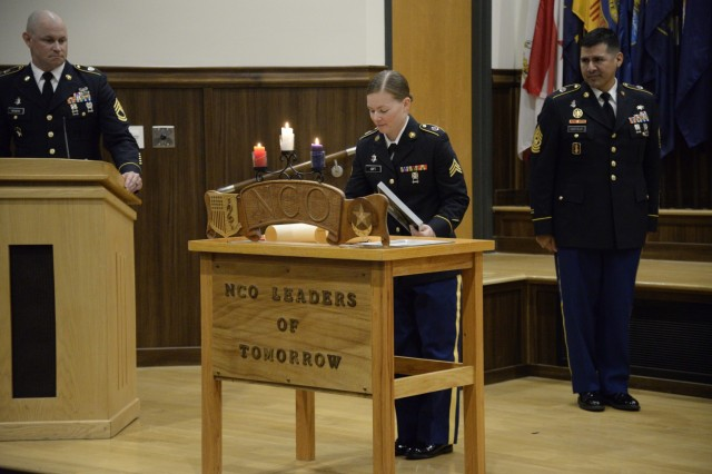 Sgt. Kristie Gift, a Biomedical Equipment Specialist for the General Leonard Wood Army Community Hospital signs the charge of a noncommissioned officer during an NCO induction ceremony on Fort Leonard Wood July 16.