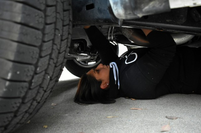 Officer Monica Garcia-Gonzalez, a Presidio of Monterey security guard, searches under a vehicle for hidden contraband during vehicle interdiction training at the Stilwell Community Center, Ord Military Community, July 13.