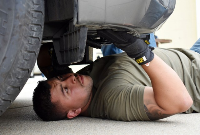 Lt. Jesus Sanchez, a Presidio of Monterey security guard, searches under a vehicle for hidden contraband during vehicle interdiction training at the Stilwell Community Center, Ord Military Community, July 13.