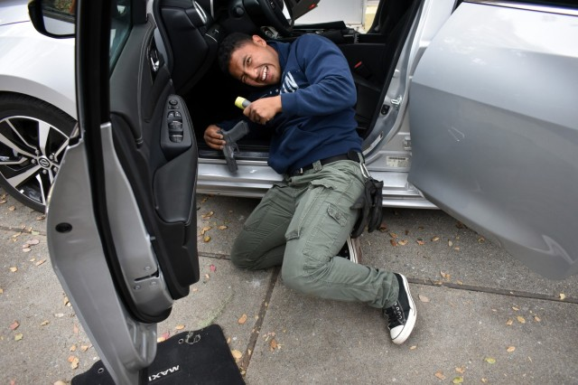 Officer Nery Cruz, a Presidio of Monterey security guard, smiles as he finds hidden contraband during vehicle interdiction training at the Stilwell Community Center, Ord Military Community, July 13.