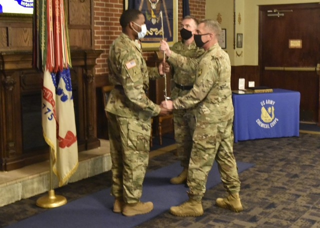 Incoming U.S. Army Chemical, Biological, Radiological and Nuclear School Regimental Chief Warrant Officer 3 Humphrey Hills (left) accepts a sword from Col. Sean Crockett, USACBRNS commandant, as outgoing Regimental Chief Warrant Officer 3 Robert Lockwood looks on during a change-of-responsibility ceremony July 22 at the CBRN Regimental Room in the John B. Mahaffey Museum Complex.