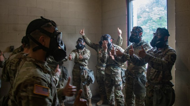 Cadre and Cadets of 7th Regiment, Advanced Camp give thumbs up while checking the capabilities of their M50 Protective Masks in the confidence chamber at Fort Knox, KY during Chemical, Biological, Radiological, and Nuclear training on July 7, 2021.   Photo by Griffin Amrein, CST Public Affairs.