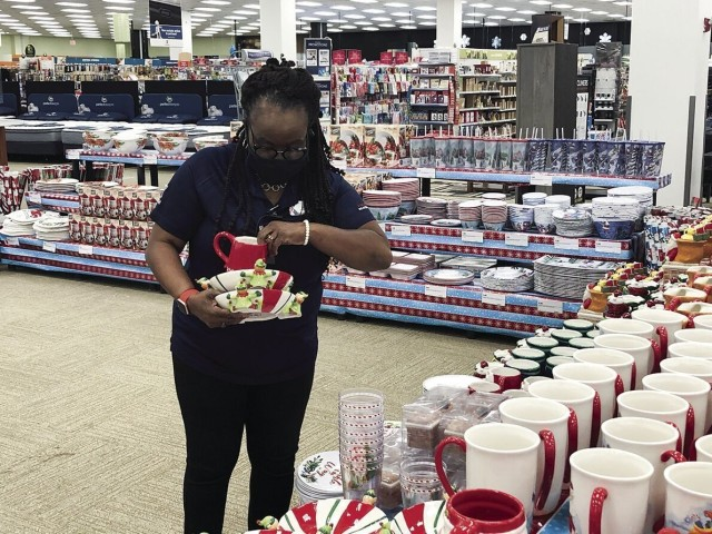 Sheilah Belt, sales area manager with the Exchange, organizes a display of Christmas items Nov. 17, 2020, in preparation for Black Friday shoppers. Families are encouraged to develop a savings plan now to avoid financial hardships during the holiday season.