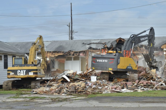 The Fort Campbell Directorate of Public Works Roads and Grounds crew works to demolish the vacated Building 873, July 19, as part of an ongoing campaign to remove World War II-era structures from the installation.