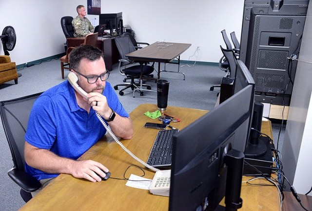 Jeff Hollaway, program analyst, calls in-bound personnel to check if they are having any issues while working in the Summer Surge Cell with Maj. Kyle Loftus, plans analyst and integration OIC, and others helping process PCSing data July 21 in Garrison Headquarters. Photo by Prudence Siebert/Fort Leavenworth Lamp