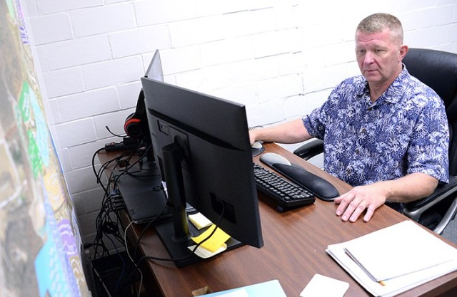 Randy Ymker, operations manager for the Summer Surge Cell, compiles numbers of processed and pending orders for the Installation Management Command daily report July 21 in Garrison Headquarters. Photo by Prudence Siebert/Fort Leavenworth Lamp