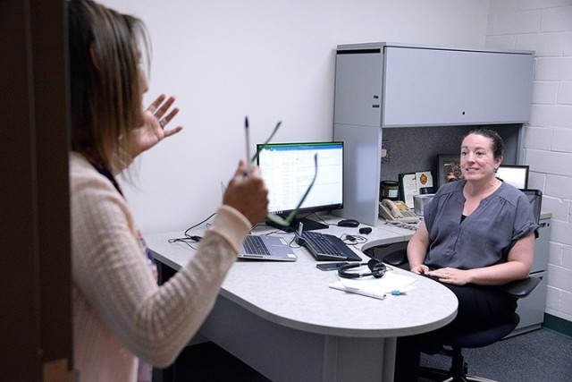 Monica Tillis, program analyst, and Joy Chalmers, knowledge management analyst, discuss how to display PCSing data while working in the Summer Surge Cell July 21 in Garrison Headquarters. Photo by Prudence Siebert/Fort Leavenworth Lamp