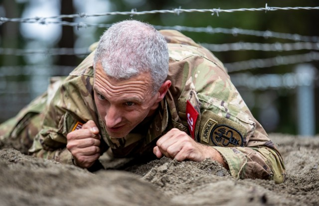 Capt. Jason Christman from Desmond Doss Health Clinic concentrates as he crawls under barbed wire on the obstacle course during Regional Health Command-Pacific's Best Leader Competition, June 15, 2021, Joint Base Lewis-McChord, Wash. Christman is part of the RHC-P team competing in the U.S. Army Medical Command Best Leader Competition, July 25-30.