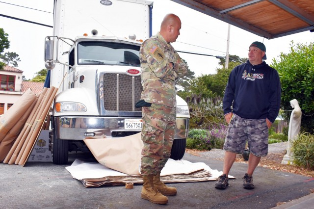 Col. Varman Chhoeung, commander of U.S. Army Garrison Presidio of Monterey, speaks with Zane Whetstone, who is moving to Japan with his family, as movers pack up his household goods in Pebble Beach, Calif., July 16. Chhoeung accompanied a quality assurance inspector with the Presidio of Monterey Transportation Office to speak with service members and their families and ensure their permanent-change-of-station moves are going well.