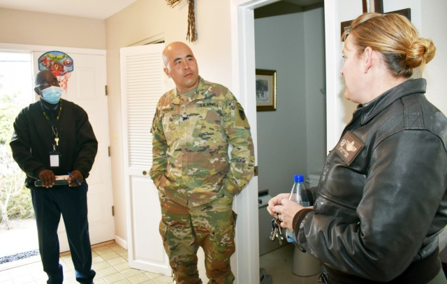 Col. Varman Chhoeung, center, commander of U.S. Army Garrison Presidio of Monterey, and  Glenn Beal, a quality assurance inspector with the Presidio of Monterey Transportation Office, greet Air Force Lt. Col. Jen Whetstone, who is moving to Japan with her family, as movers pack up her household goods in Pebble Beach, Calif., July 16. Chhoeung accompanied Beal to speak with service members and their families and ensure their permanent-change-of-station moves are going well.