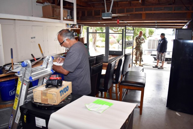 Movers pack the household goods of the Whetstone family as Col. Varman Chhoeung, commander of U.S. Army Garrison Presidio of Monterey, speaks with Zane Whetstone, who is moving to Japan with his family, in Pebble Beach, Calif., July 16. Chhoeung accompanied a quality assurance inspector with the Presidio of Monterey Transportation Office to speak with service members and their families and ensure their permanent-change-of-station moves are going well.
