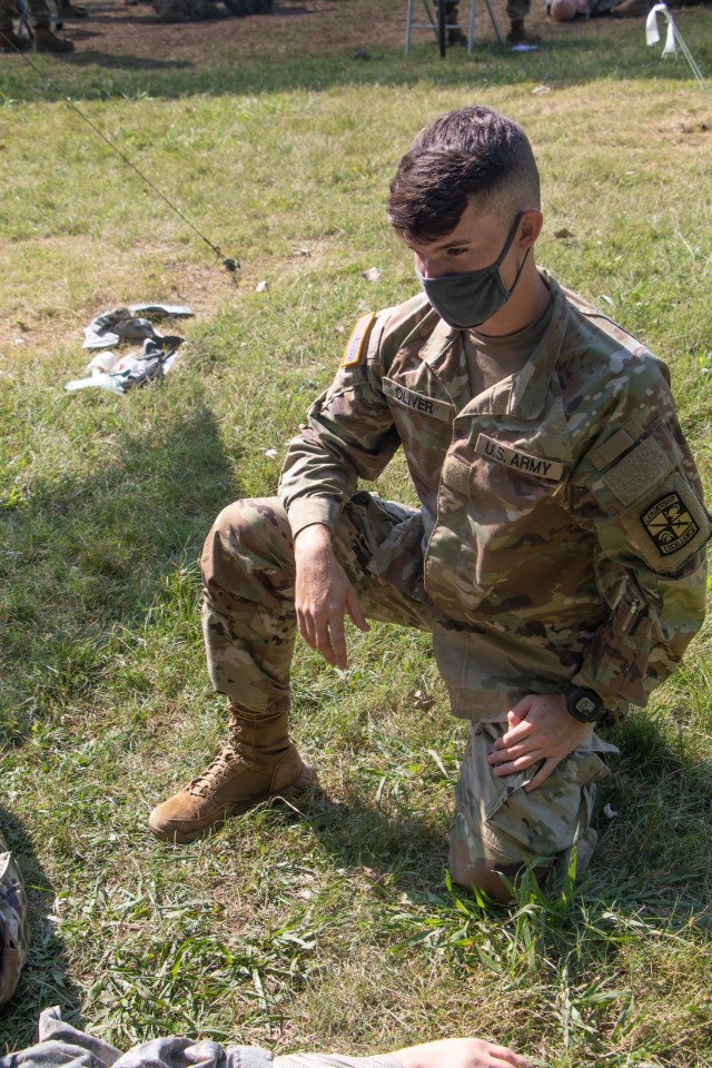 Cadet Randy Oliver, from University of Puerto Rico-Río Piedras Campus, watches his battle buddy complete his tactical combat care test at Warrior Skills at Advanced Camp at Fort Knox, Ky on July 7, 2021. | Photo by Marissa Wells, CST Public Affairs Office.