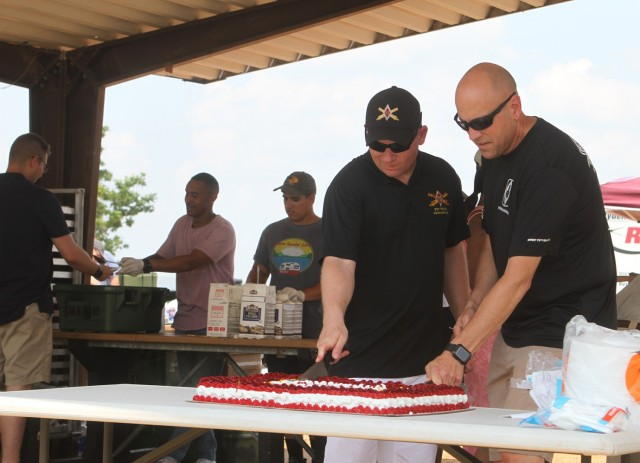 The 75th Field Artillery Brigade command team of Command Sgt. Maj. John Black and Col. David Norris make the ceremonial first cuts of the 100th anniversary cake.
