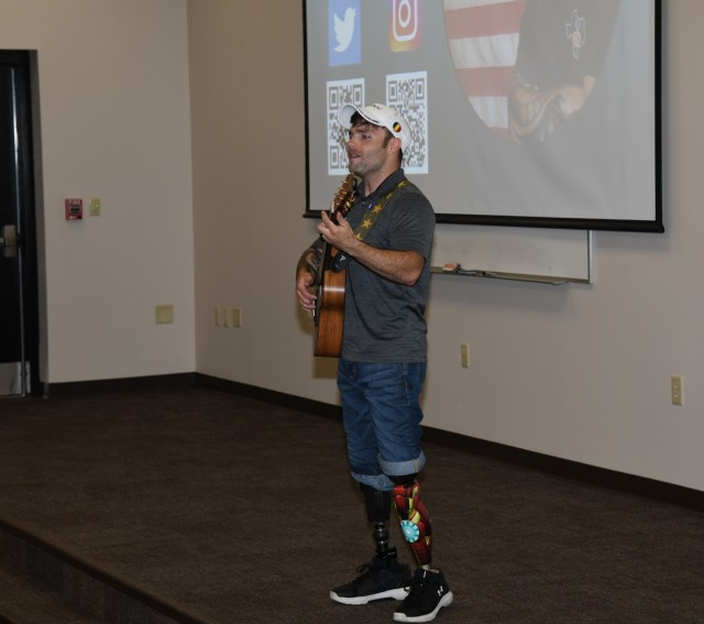Decorated U.S. Army veteran and motivational speaker J.P. Lane performs a song as part of a presentation to students from the Aviation Captains Career Course, Basic Officer Leaders Course, and Warrant Officer Basic Course at Fort Rucker July 20, 2021. (U.S. Army photo by Kelly Morris)