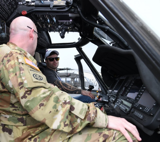 Decorated combat veteran and motivational speaker J.P. Lane sits in the cockpit of a UH-60 Black Hawk helicopter at Lowe Army Heliport with Chief Warrant Officer 3 John Cornelius, an aviator from the U.S. Army Aviation Center of Excellence's command aviation branch, during a tour of Fort Rucker, Alabama, July 19, 2021.