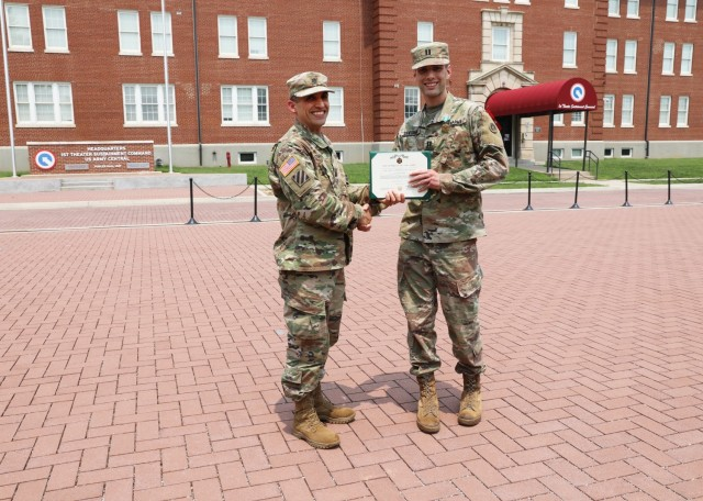 Lt. Col. Richard Gorini, staff judge advocate, 1st Theater Sustainment Command, presents an Army Commendation to Capt. Thomas Sandbrink, contract and fiscal law attorney, 1st TSC, July 21 at Fort Knox, Kentucky.
