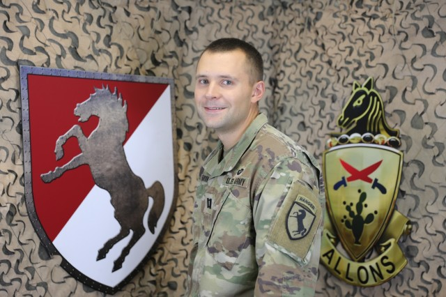 Chaplain (Capt.) Aaron Fabian, Chaplain for 1st Squadron, 11th Armored Cavalry Regiment poses with the Ironhorse shield and 11th Armored Cavalry Regiment distinctive unit insignia in the Regimental Public Affairs Office, Fort Irwin, Calif on July 16th, 2021.  (U.S. Army photo by Pvt. James Newsome)