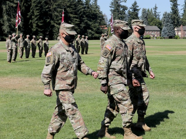 Brig. Gen. Jack M. Davis, left, outgoing commanding general of Regional Health Command-Pacific; Lt. Gen. R. Scott Dingle, center, the Army Surgeon General and commanding general of U.S. Army Medical Command; and Brig. Gen. Edward H. Bailey, right, incoming commanding general of RHC-P, walk from Watkins Field during the change of command ceremony, July 26, 2021, at Joint Base Lewis-McChord, Washington.