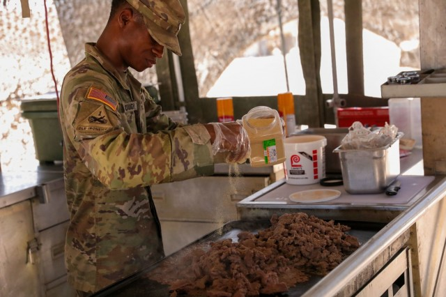 Spc. Courtney Roseborough, assigned to Regimental Support Squadron, 11th Armored Cavalry Regiment, seasons a lunch entree at the field feeding site, National Training Center and Fort Irwin, Calif., July 20th, 2021. He is part of the 11th Armored Cavalry Regiment field feeding team representing the National Training Center for the Philip A. Connelly Active Army Kitchen Competition.  (U.S. Army photo by Pvt. James Newsome, 11th ACR Public Affairs Office)