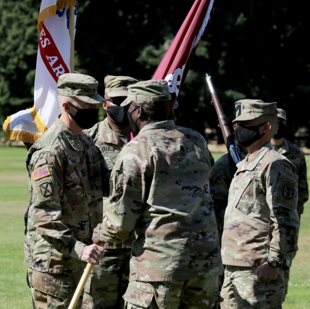 Lt. Gen. R. Scott Dingle, center, the Army Surgeon General and commanding general of U.S. Army Medical Command, passes the colors to Brig. Gen. Edward H. Bailey, incoming commanding general of RHC-P, during the change of command ceremony, July 26, 2021, at Joint Base Lewis-McChord, Washington. At right is Brig. Gen. Jack M. Davis, the outgoing commanding general of RHC-P.