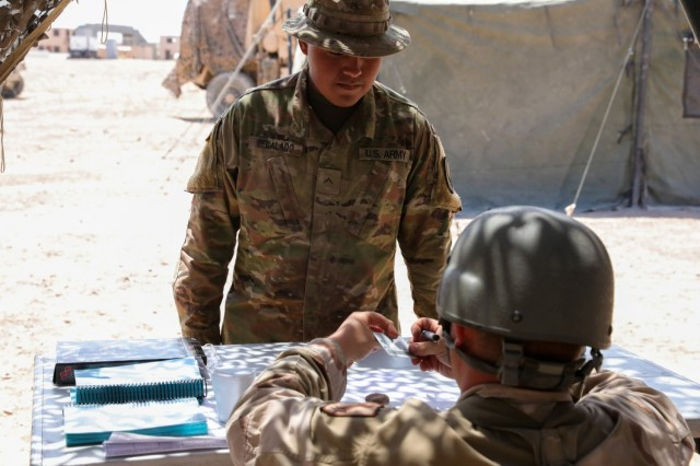 Pvt. Regalado, assigned to Regimental Support Squadron, 11th Armored Cavalry Regiment, presents his common access card for admittance into the field feeding site, National Training Center and Fort Irwin, Calif., July 20th, 2021. Soldiers at the field feeding site must participate in headcount procedures before entering the serving line.   (U.S. Army photo by Pvt. James Newsome, 11th ACR Public Affairs Office)