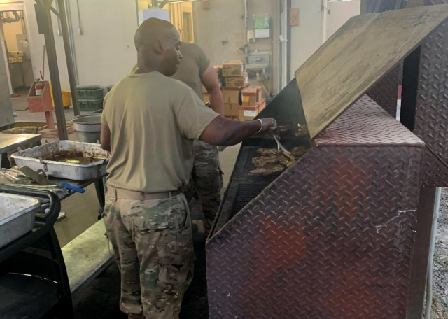 """Army Reserve Master Sgt. Lloyd Cossey, who deployed to the U.S. Central Command area of operations at Camp Arifjan, Kuwait, with the Indianapolis-based 310th Sustainment Command (Expeditionary), grills steaks at the North Dining Facility at Bagram Airfield, Afghanistan during his 29-day assignment there that ended July 2, 2021, when the DFAC closed. Cossey is one of four """"Brickyard"""" Army culinary specialists, or 92G's, tasked to support the dining facility that served hot meals to both Coalition and U.S. forces. (Photo courtesy of Sgt. Nicole Hall)"""
