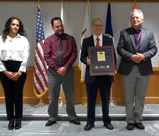 Mr. John Taylor (Program Officer, Abrams Powertrain) accepts the 2020 Lean Six Sigma Excellence Award for Process Improvement Non-Enterprise Level Non-Gated  Project on behalf of Program Executive Office, Ground Combat Systems.