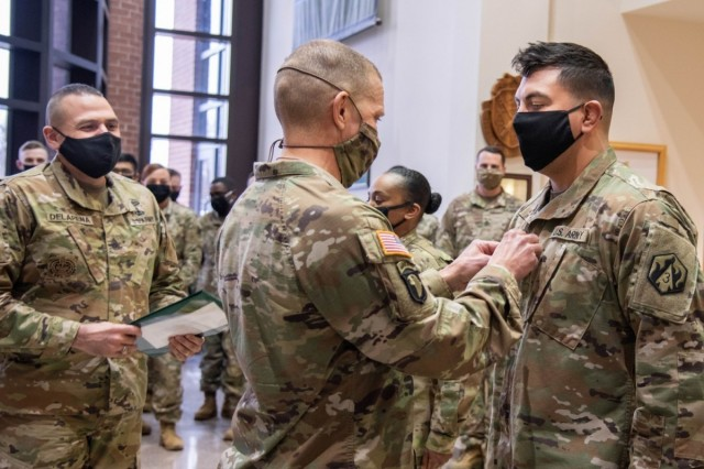 Sgt. Maj. of the Army Michael Grinston (center) assists with the promotion of Sgt. 1st Class Julio De La Cruz Feb. 9, 2021, in the foyer of the U.S. Army Military Police School command section. Grinston visited Fort Leonard Wood to engage with leaders and Soldiers.