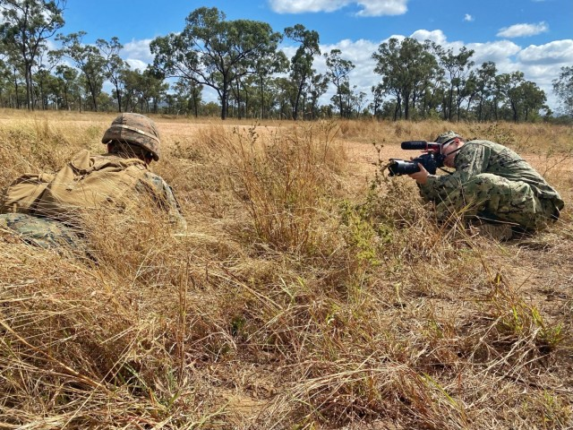 Mass Communication Specialist 1st Class Jen S. Martinez, a member of the Combined Joint Information Bureau, captures video of a U.S. Marine during a combined urban clearance during Exercise Talisman Sabre 21 in Townsville Training Area, Queensland, Australia, July 27, 2021. She is a Navy Reservist with Navy Office of Information, U.S. Pacific Fleet, and is on her first annual training. Australian and U.S. Forces combine biennially for Talisman Sabre, a month-long multi-domain exercise that strengthens allied and partner capabilities to respond to the full range of Indo-Pacific security concerns. (U.S. Navy photo by Lt. Travis Weger)
