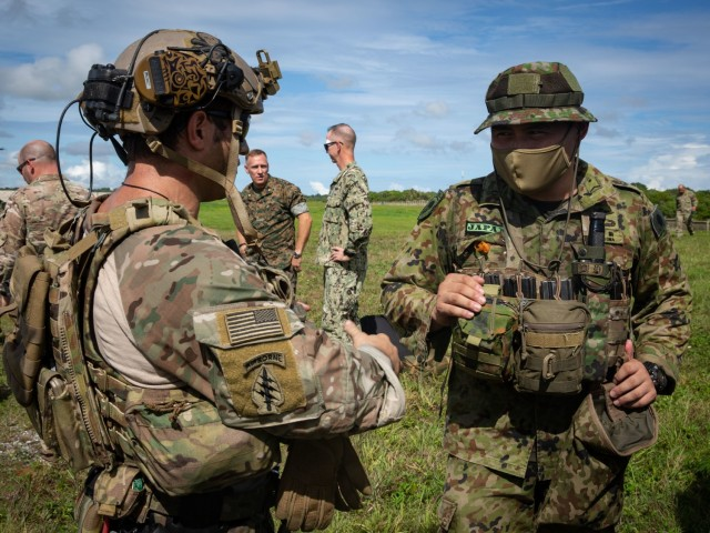 ANDERSEN AIR FORCE BASE, Guam – A U.S. Army Green Beret with 1st Battalion, 1st Special Forces Group (Airborne), discusses mission planning with a member of the Japan Ground Self-Defense Force July 30, 2021. Defender Pacific 21 is a U.S. Army Pacific exercise that uses the National Defense Strategy by practicing the strategic deployment, command and control, and employment of combat credible forces into the region, and supports the Indo-Pacific Command's Joint war fighting concepts. DP 21 demonstrates the Theater Army's ability to rapidly surge combat-ready forces into and across the theater. (U.S. Army photo by Spc. Thoman Johnson)