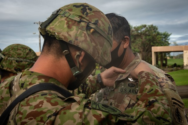 BARRIGADA, Guam – A member of the Japan Ground Self-Defense Force pins Japanese Jump Wings on a U.S. Army Green Beret assigned to 1st Battalion, 1st Special Forces Group (Airborne), during a wing exchange ceremony July 31, 2021. Airborne personnel from JGSDF and the U.S. Army parachuted onto a drop zone together at Andersen Air Force Base, Guam, the day prior during bilateral airborne operations in support of Exercise Forager 21. Forager 21 is a U.S. Army Pacific exercise designed to test and refine the Theater Army's ability to flow landpower forces into the theater, execute command and control of those forces, and effectively employ them in support of our allies, partners, and national security objectives in the region. (U.S. Army photo by Spc. Thoman Johnson)