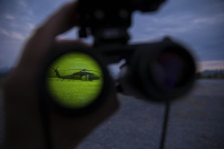 Soldiers resupply an Army UH-60 Black Hawk helicopter during aerial gunnery training as seen through a night vision lens at Fort Drum, N. Y., June 13, 2021.