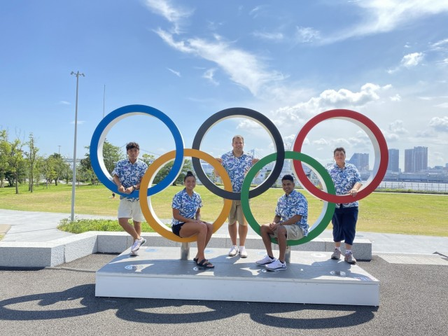 From left: Gaku Hashimoto, Marshallese delegation member; Colleen Furgeson, athlete; Johnathan Jordan, swim coach; Phillip Kinono, athlete; and Amy LaCost, chef de mission, visit an Olympic rings installation inside the Olympic Village near Tokyo's Rainbow Bridge in July 2021. Furgeson and Kinono represent the Republic of the Marshall Islands in this year's Summer Games.