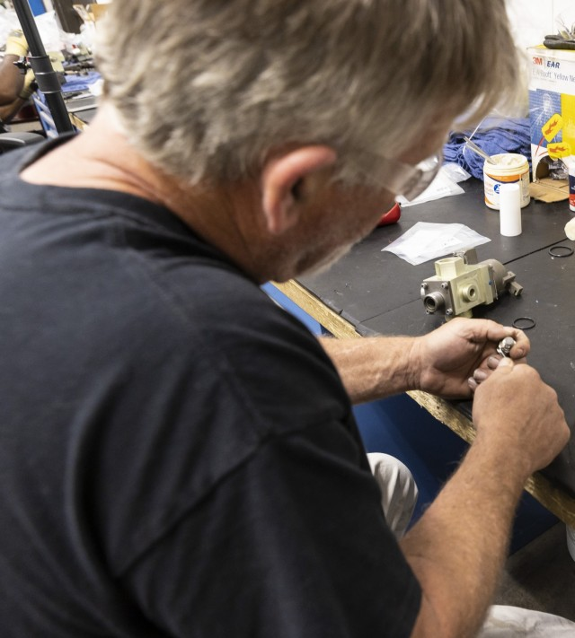 Bubba Hughes, artillery mechanic, cleans a valve part in preparation for a new O-ring at Anniston Army Depot.