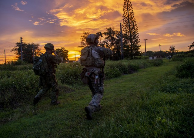 BARRIGADA, Guam -- A Green Beret assigned to 1st Battalion, 1st Special Forces Group (Airborne), maneuvers to the objective area alongside a member of the Japan Ground Self-Defense Force during Defender Pacific 21 on July 30, 2021. DP21 is one of many U.S. Army Pacific exercises and activities occurring during summer 2021 which implements the National Defense Strategy by integrating Land Power in the Indo-Pacific to enable the Joint Force; build trust and interoperability with allies and partners; and employ emerging multi-domain capabilities to support innovation and experimentation. (U.S. Army photo by Spc. GaoZong Lee) (This photo has been altered for security purposes.)