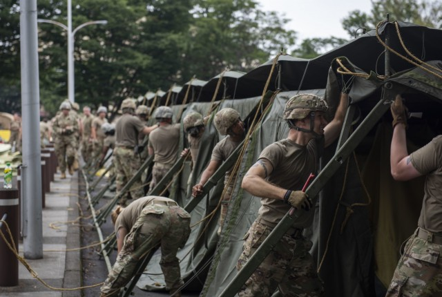 Soldiers from the 311th Field Hospital from Blacklick, Ohio, prepare to lower a tent after an Army field exercise at Yokota Air Base, Japan, June 25, 2021. With the assistance of the 18th Medical Command and the 374th Airlift Wing, the 311th Field Hospital received the opportunity to mock forward deploy and practice setting up a 32-bed hospital in an unfamiliar location. (U.S. Air Force photo by Senior Airman Hannah Bean)