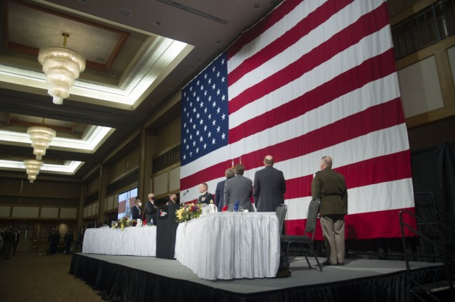 """Staff Sgt. Richard Scarlett of the Maneuver Center of Excellence Band (Fort Benning, Ga.) sings the National Anthem at the podium during the annual Armed Forces Celebration Luncheon hosted by the Huntsville/Madison County Chamber Aug. 4 at the Von Braun Center, Huntsville, Ala. The luncheon culminated Armed Forces Celebration 2021 under this year's theme """"Redstone Arsenal: 80 Years Supporting Our Nation."""" Attendees were required to wear facemasks, sanitize and practice social distancing. Huntsville Hospital set up a COVID-19 vaccine center at the event."""