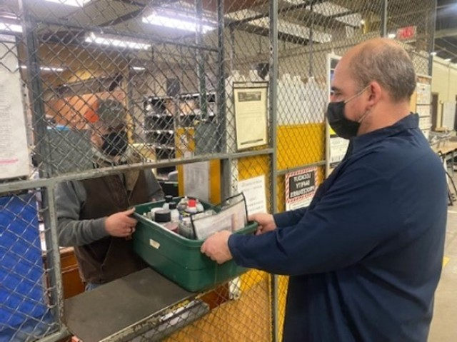 """Rocky Gray (right) receives a """"to go tub"""" of Petrol, Oil, and Lubricants products from Garrett Koehler (left) for daily use at the Fleet Management Expansion at Fort Leonard Wood, Missouri."""