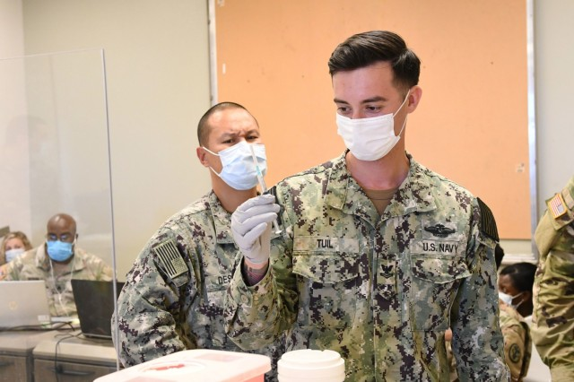 Hospital Corpsman Second Class David Tuil prepares a Pfizer COVID-19 vaccine syringe at a joint-service COVID-19 vaccination event at the Navy Exchange Pearl Harbor, Hawaii on July 16, 2021. The joint-service event was staffed by Hospital Corpsman from Navy Medicine Readiness and Training Command Pearl Harbor and U.S. Army medical staff from Tripler Army Medical Center. The free event kicked off on July 16 and will run for four weekends in July and August from 9 am to 2 pm. All TRICARE beneficiaries, as well as government civilians and non-appropriated fund (NAF) employees are eligible to receive their vaccine at the event.