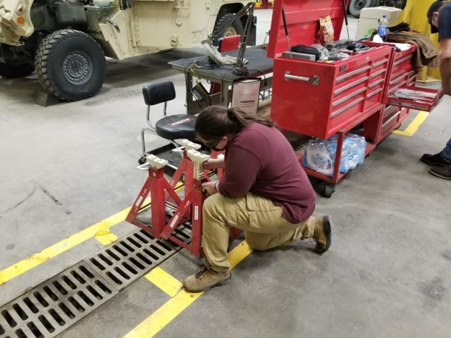 Kimberly Hammett, Fort Leonard Wood Fleet Management Expansion, inspects a jack stand prior to use.